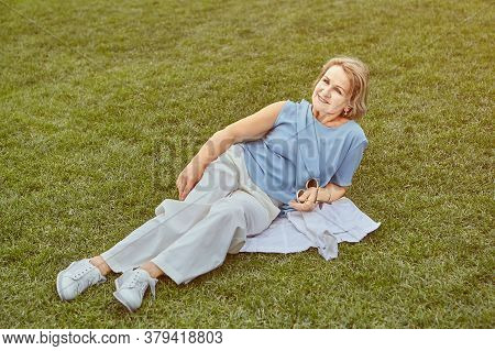 Elderly Caucasian Active Woman About 62 Years Old Is Lying On The Grass In The Public Park. She Wear