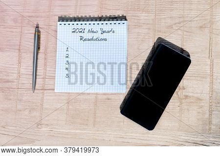 New Year Concept - 2021 Number And Text On Notepad. Smartphone, Notepad And Pen On A Wooden Table.