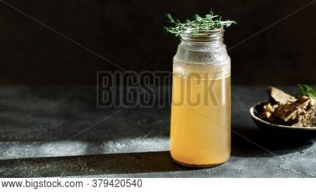 Fresh Vegetable Bone Broth In Glass Jar With Herb On Dark Gray Background. Healthy Dieting Food Are