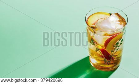 Sparkling Cold Brew Peach Tea With Thyme In Glass On Green Paper Background Close-up. Refreshing Sum