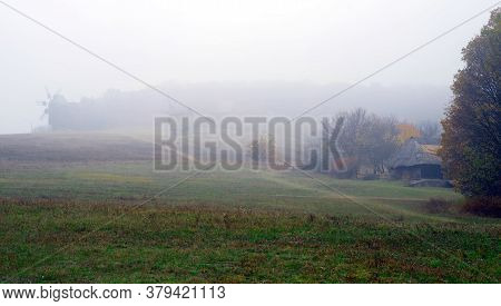 Foggy Autumn Landscape With A Road On A Hill In The Middle Of A Field With Windmills And A Wooden Hu