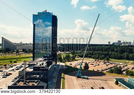 A View From The Height Of The Tallest Car Crane, Which Is Open In The Parking Lot Near The Glass Bui