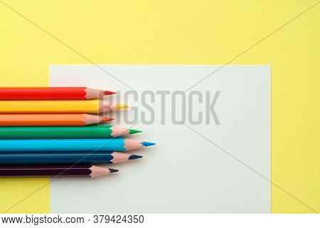Colorful Pencils On White Paper On Yellow Background, Flat Lay, Close-up. Set Of Rainbow Pencils, Co