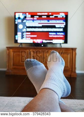 Feet Up Watching Television With Television Out Of Focus