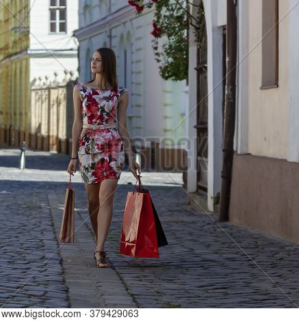 Young Woman With Shopping Bags Walking In A Small Cobblestone Street In A City.