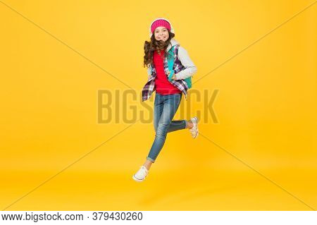 Life Is A Daring Adventure. Happy Child Jump Yellow Background. Energetic Girl Wear Backpack In Casu
