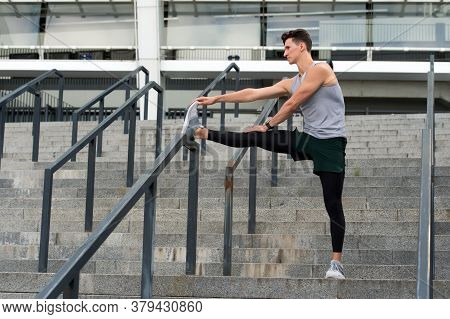 Determined Male Athlete Stretching Legs Outdoor Preparing For Workout. Warm Up Firstly. Keeping Thos