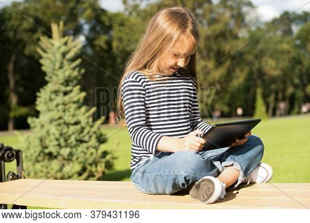 Experience It. Little Girl Use Tablet In Summer Park. Modern Computing Device. Touchscreen Interface