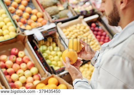 Over shoulder view of bearded man standing at food counter and buying citrus fruits to strengthen immunity at market