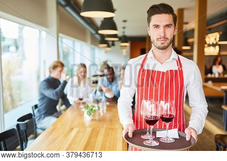 Young man serving as a waiter in training serves wine on a tray