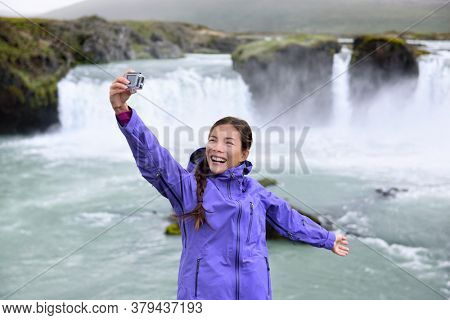 Iceland tourist taking selfie photo with smart phone by Godafoss waterfall. Happy young woman tourists enjoying icelandic nature landscape visiting famous tourist destination attraction, Iceland