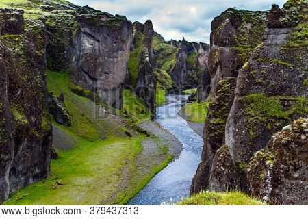 The mysterious and beautiful canyon in Iceland - Fyadrarglyufur Canyon. Sheer cliffs stand along a stream with melted glacial water. The concept of active, eco and photo tourism