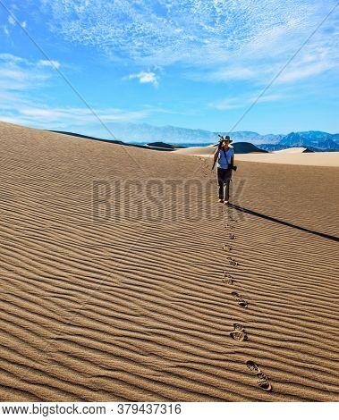 USA. Mesquite Flat Sand Dunes, Death Valley, California. Light sand waves from the desert wind. Woman with a camera and a tripod goes among the dunes. Concept of active and photo tourism