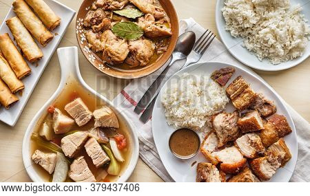 filipino dinner with sinigang, lechon kawali, and chicken adobo top down composition