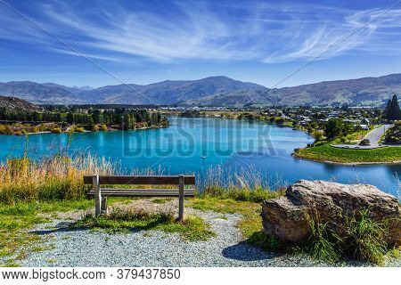 The picturesque lake Dunstan near the town of Cromwell. Cozy bench set on the lake. South Island, New Zealand. The concept of ecological and photo tourism