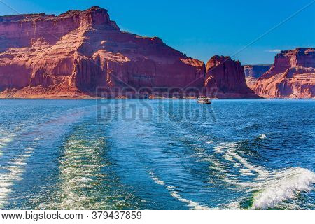 Excursion on a pleasure boat on Lake Powell among rocks of red sandstone. Lake Powell is a reservoir on the Colorado River, USA. Concept of active and photo tourism