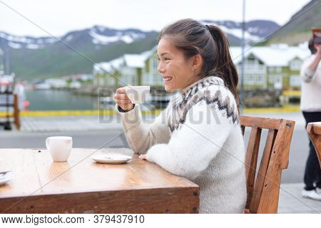 Woman drinking coffee on sidewalk cafe on Iceland. Girl tourist sipping enjoying coffee from cup wearing icelandic sweater. People visiting iceland sitting outdoors in Siglufjordur, North Iceland.
