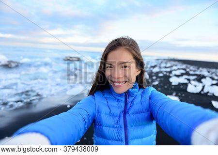 Adventure selfie by trave explorer woman on Iceland Diamond Beach. Woman tourist in amazing landscape Ice beach, Breidamerkursandur by jokulsarlon glacial lagoon / glacier lake nature.