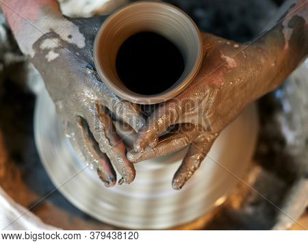 Potters hands are creating earthenware on potters wheel. Concept of natural materials, hand made and creativity