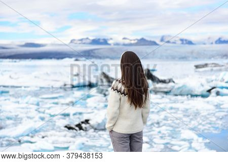 Iceland travel tourist enjoying view of nature landscape Jokulsarlon glacial lagoon on Iceland. Woman standing outdoors by tourist destination landmark attraction. Vatnajokull National Park.