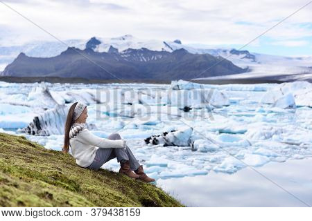 Iceland tourist enjoying Jokulsarlon glacial lagoon. Woman visiting destination landmark attraction glacier lake, Iconic Vatnajokull nature landscape.