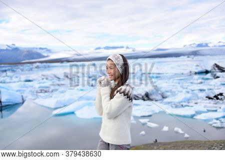 Iceland travel tourist enjoying nature landscape Jokulsarlon glacial lagoon on Iceland. Portrait of Woman standing outdoors by tourist destination landmark attraction. Vatnajokull National Park.