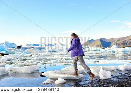 Iceland travel tourist walking on ice looking at view of nature landscape Jokulsarlon glacial lagoon on Iceland. Woman hiking by tourist destination landmark attraction. Vatnajokull National Park.