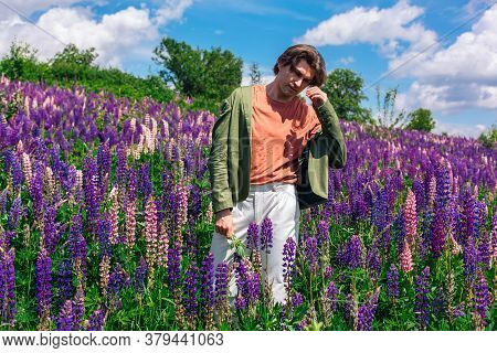 Tall Handsome Man Standing On Lupine Flowers Field Holding Lupine Flowers In Hand