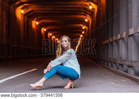 Young Woman Sitting Next To A Tunnel With Lights