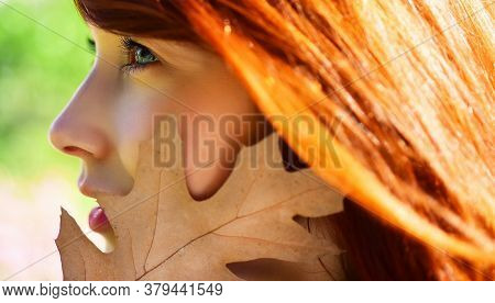 Autumn Girl Close Up Portrait. Woman Eyes With Yellow Maple Leaves On Nature Background. Redhead Gir