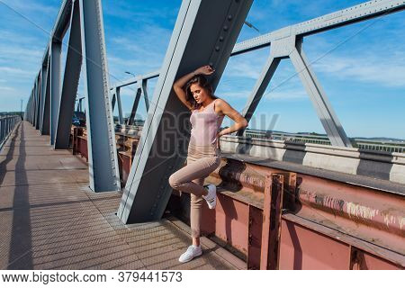 Pretty Young Woman Posing On The Old Rusty Transport Bridge Over The River During Sunset.