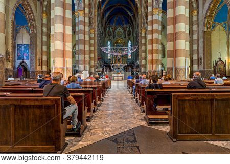 ALBA, ITALY - JUNE 14, 2020: People sitting on wooden pews during mass inside of San Lorenzo Roman Catholic cathedral dedicated to Saint Lawrence in small town of Alba in Piedmont, Northern Italy.