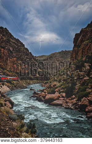 Lightning Striking In The Distance As Train Engine Rides Along A River Inside A Gorge Or Ravine Colo