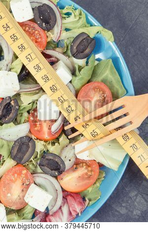 Tape Measure And Fresh Greek Salad With Feta Cheese And Vegetables. Healthy Meal As Source Natural V