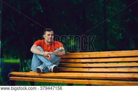 Adult Man Resting On Bench. Adult Male In Red T Shirt And Jeans Sitting On Bench And Looking Away Wh
