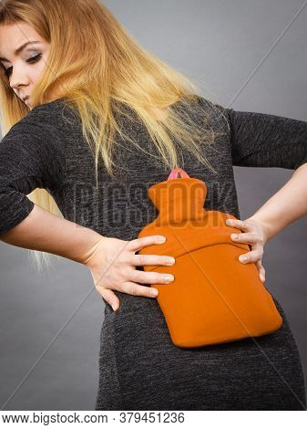 Woman Having Strong Back Pain Holding Hot Red Water Bottle On Her Spine. Health Care, Remedy For Pai