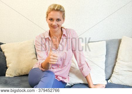 Pretty Woman 30 -35 Years Old At Home Sitting On The Couch Showing A Gesture Okay. Approval Mark