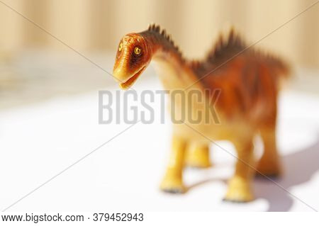 An Unfortunate Orange Plastic Toy Dinosaur At Playground