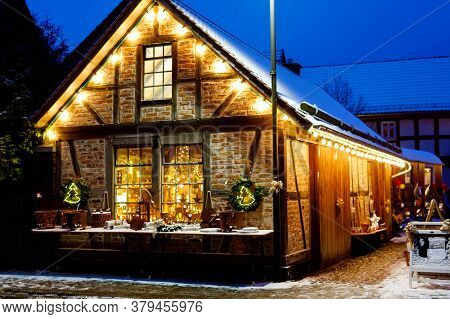 Decorated House On Christmas In Germany Covered With Snow. Festive Lights, Garlands. Beautiful Holid