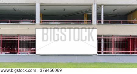 White Advertisement Poster Located On Metal Parking Lot Fence Of Red Colour Near Green Flowerbed On
