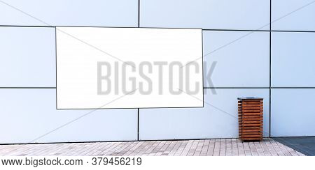 White Banner Mockup On Local City Building Wall At Paved Sidewalk And Decorative Brown Rubbish Bin O