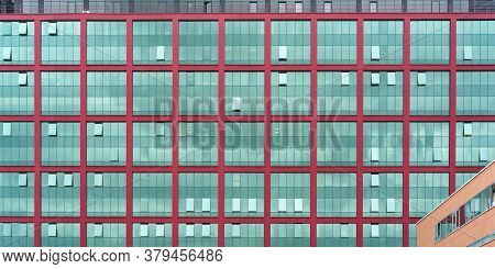 Local Corporate Office Building Wall Of Red Colour With Large Panoramic Windows Reflecting Blue Skys