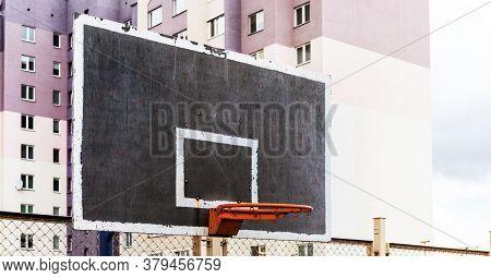 Orange Basketball Hoop On Blackboard At Sports Ground Against Purple City Dwelling Buildings Side Vi