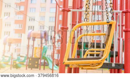 Orange Metal Swings On Chains Hang Against Playground Attractions And Colorful Dwelling Building Clo