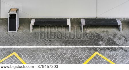 Grey Benches With Concrete Supports And Rubbish Bin Located On Pavement With Yellow White Road Marki