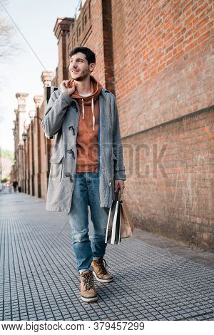 Young Man Holding Shopping Bags While Walking On The Street.