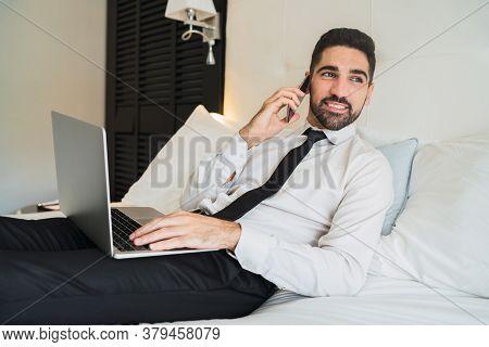 Businessman Talking On Phone At Hotel Room.