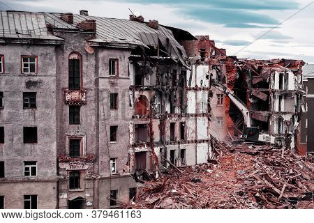 An Excavator Demolishes An Old Dilapidated Brick House In The City Of Norilsk.. Block Of Flats Demol