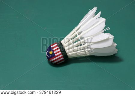 Used Shuttlecock And On Head Painted With Malaysia Flag Put Horizontal On Green Floor Of Badminton C