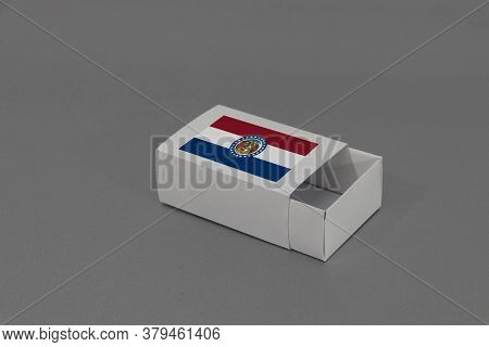 Missouri Flag On White Box On Grey Background, Paper Packaging For Put Match Or Products. The Concep